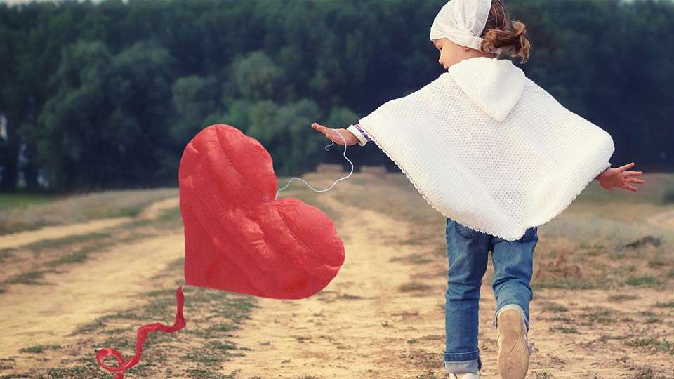 Little girl playing with red heart balloon - Being loving is beautiful