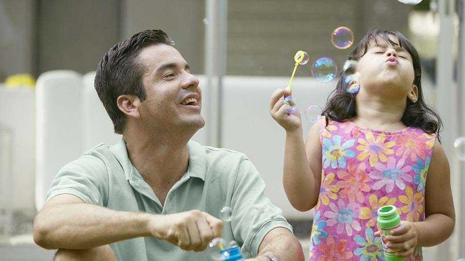 Father and daughter blowing bubbles - Creating a Future for Our Children