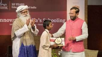 """Sadhguru and Hon. Union Minister Human Resource Development Shri Prakash Javadekar giving an award to an Isha Vidhya student"""
