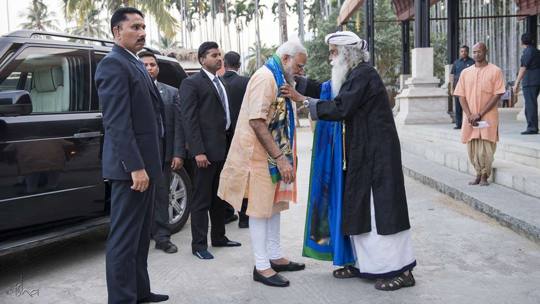 Sadhguru offering the now-famous Adiyogi stole to the PM in front of the Suryakund