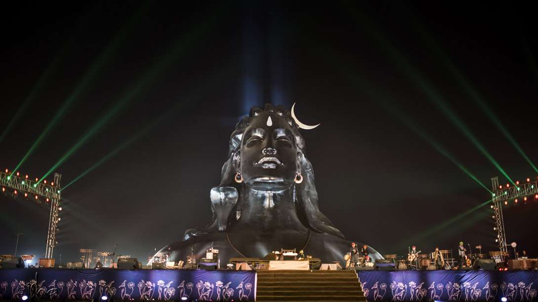 Pillars of light rising from Adiyogi into the night sky as the Rajasthan Roots with Kutle Khan perform on stage