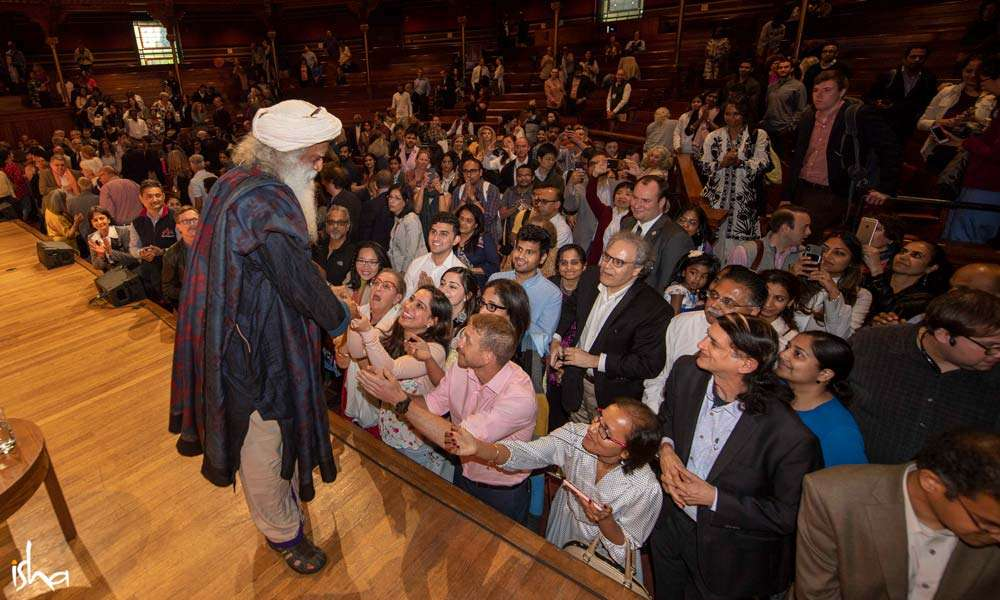 Enthusiastic members of the audience gather around Sadhguru after the talk